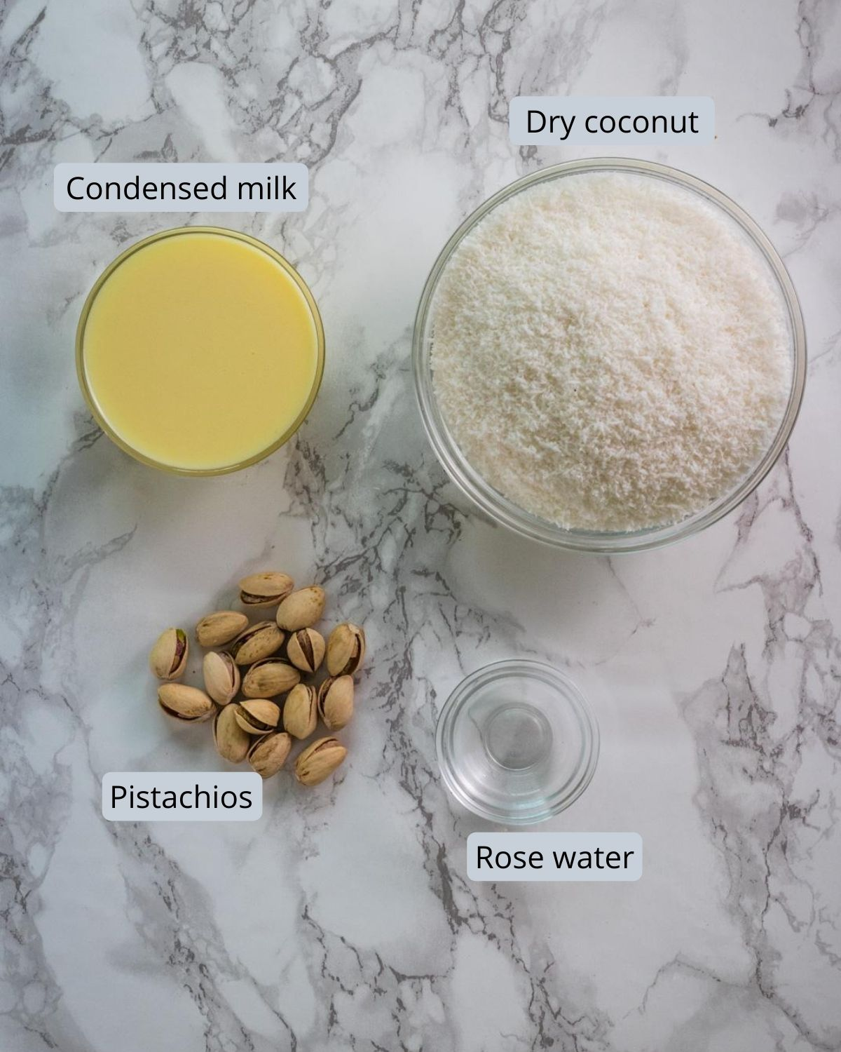 ingredients used in coconut burfi includes dry coconut, condensed milk, rose water, pista