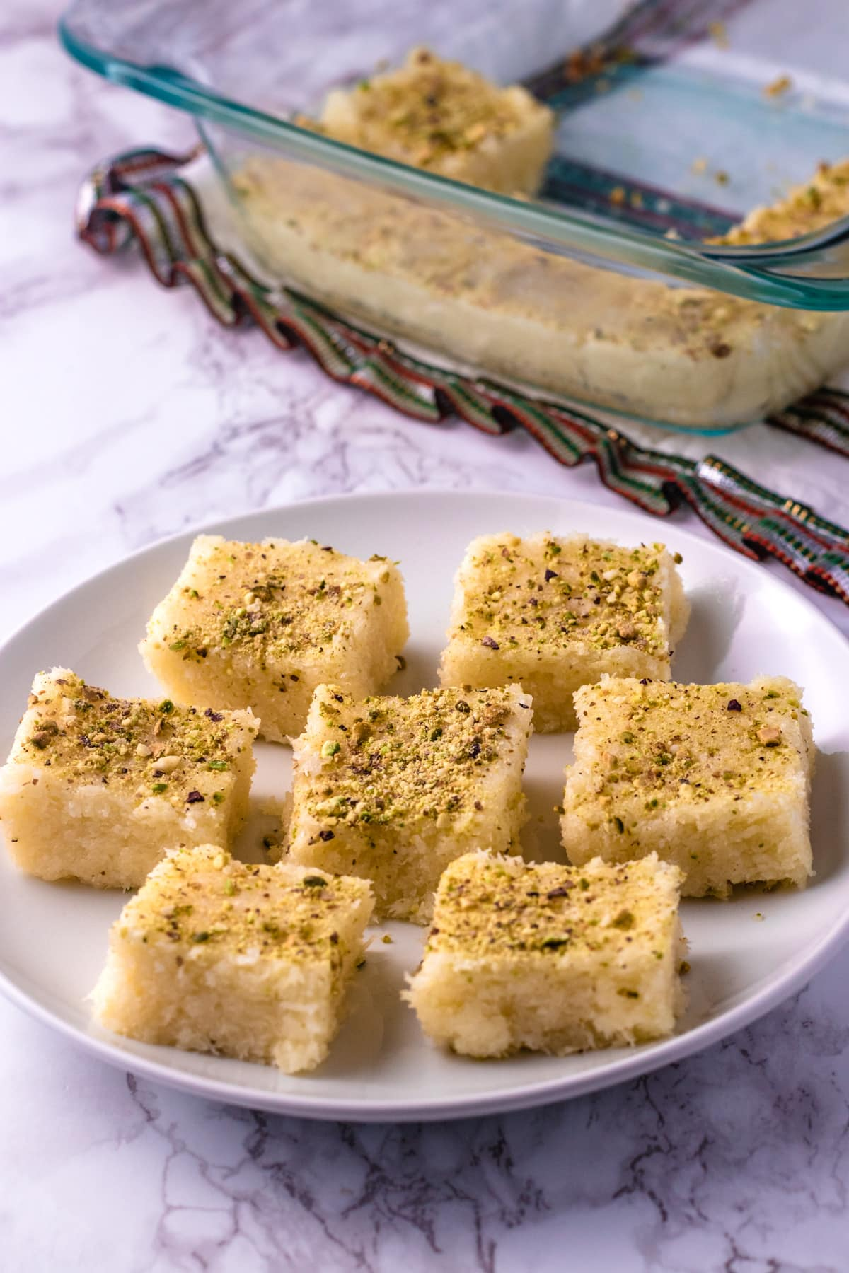 7 pieces of coconut burfi in a plate with few pieces in a pan in the back