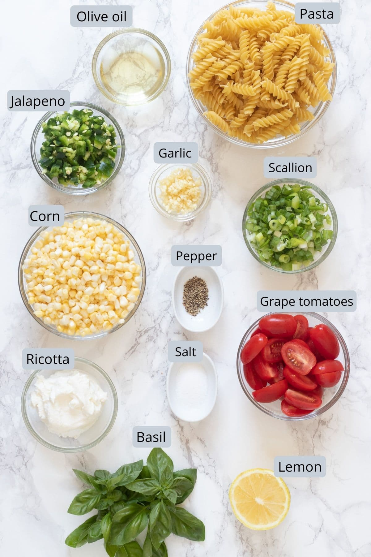 image of ingredients used in corn pasta includes pasta, corn, jalapeno, garlic, scallions, basil, lemon, ricotta, tomatoes, salt, pepper, oil
