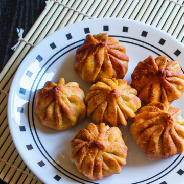 Image of fried modaks on plate with bamboo mat underneath.