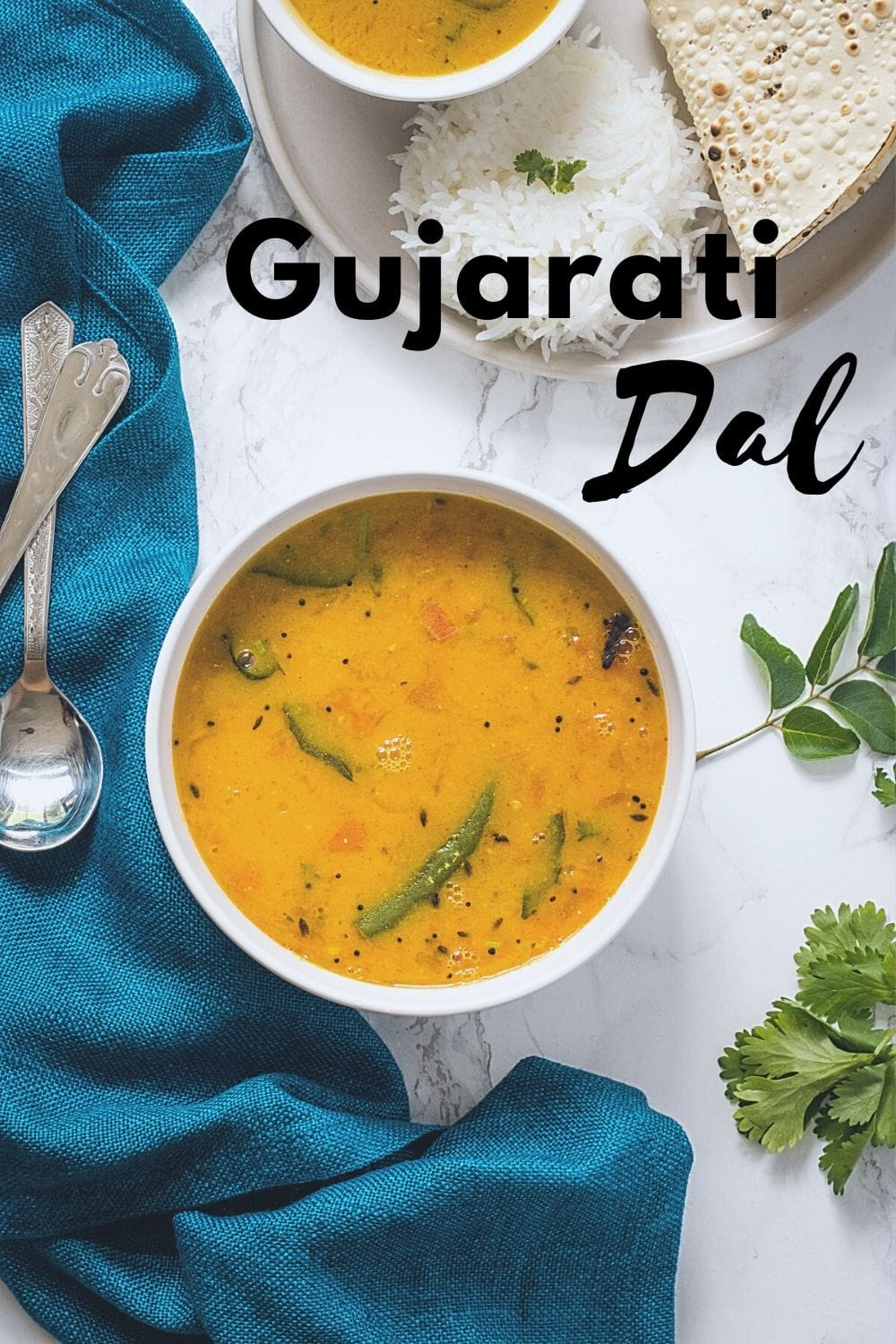 Gujarati dal in a bowl with rice and papad on side with napkin, spoons and cilantro leaves laid around the bowl