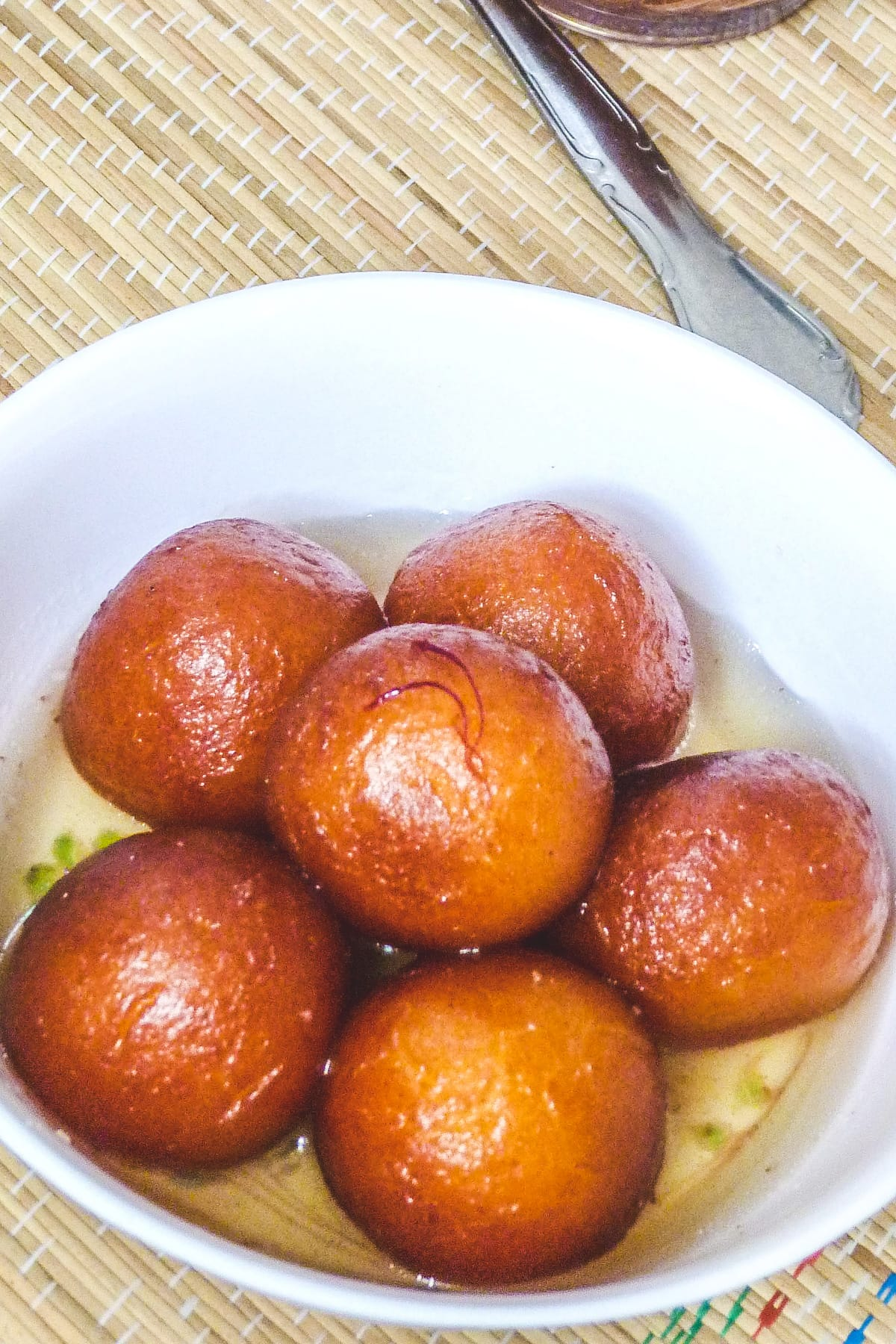 6 gulab jamun with sugar syrup in a bowl with spoon on side.