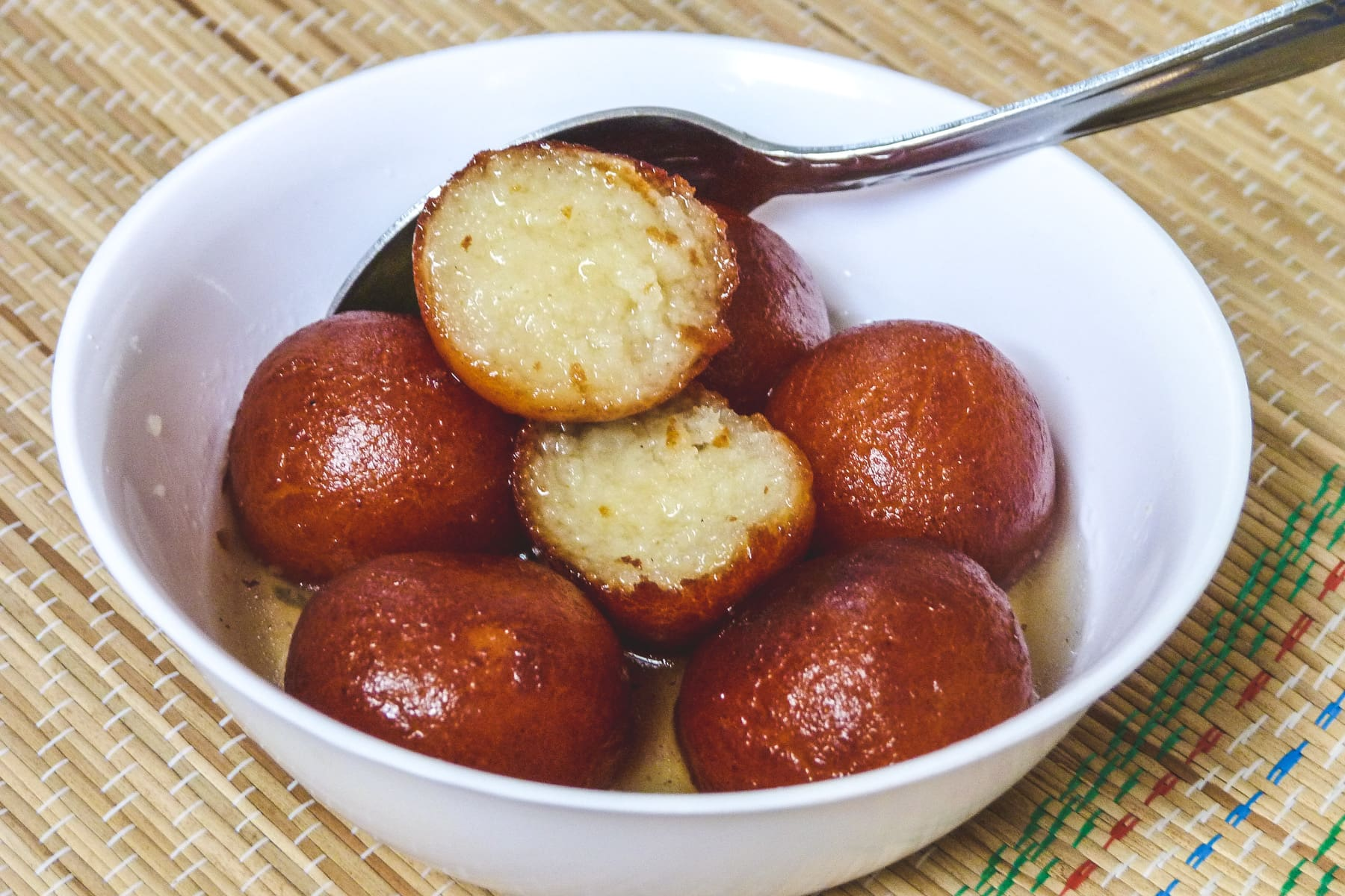 Gulab jamun in a bowl with one jamun cut open with a spoon