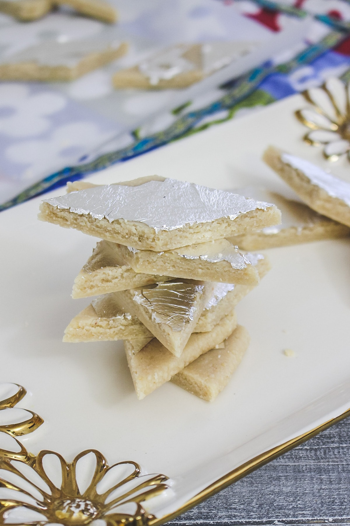 stack of kaju katli in a gold flower decorated plate