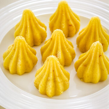 7 modak peda arranged on a white plate