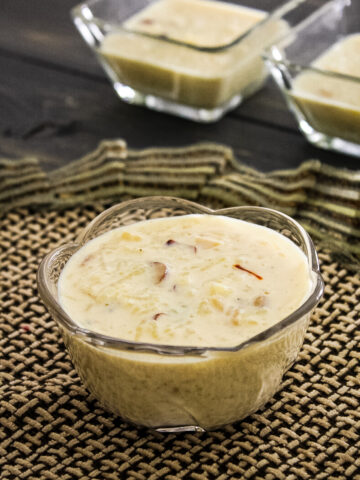 kheer in a bowl with decorative napkin underneath and 2 bowls of kheer in the back
