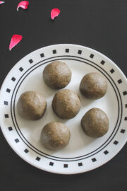 6 bajra ladoo on a plate with rose petals on side as a garnish