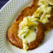 3 malpua in a plate and topped with rabdi and garnish with nuts