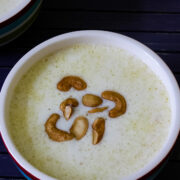 Close up image of paal payasam in a bowl with garnish of fried cashews.
