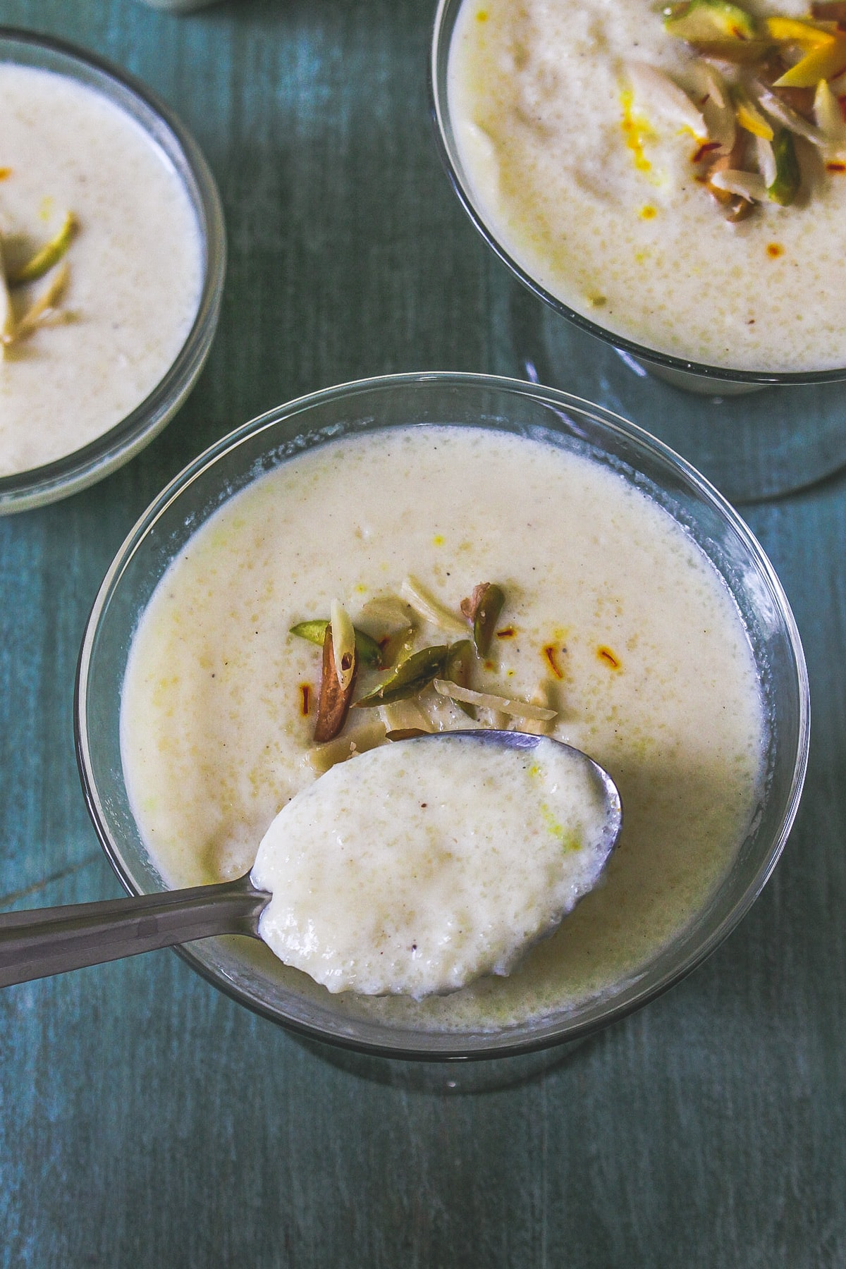 phirni served in 3 individual bowls and a spoonful of taken from one bowl, ready to eat