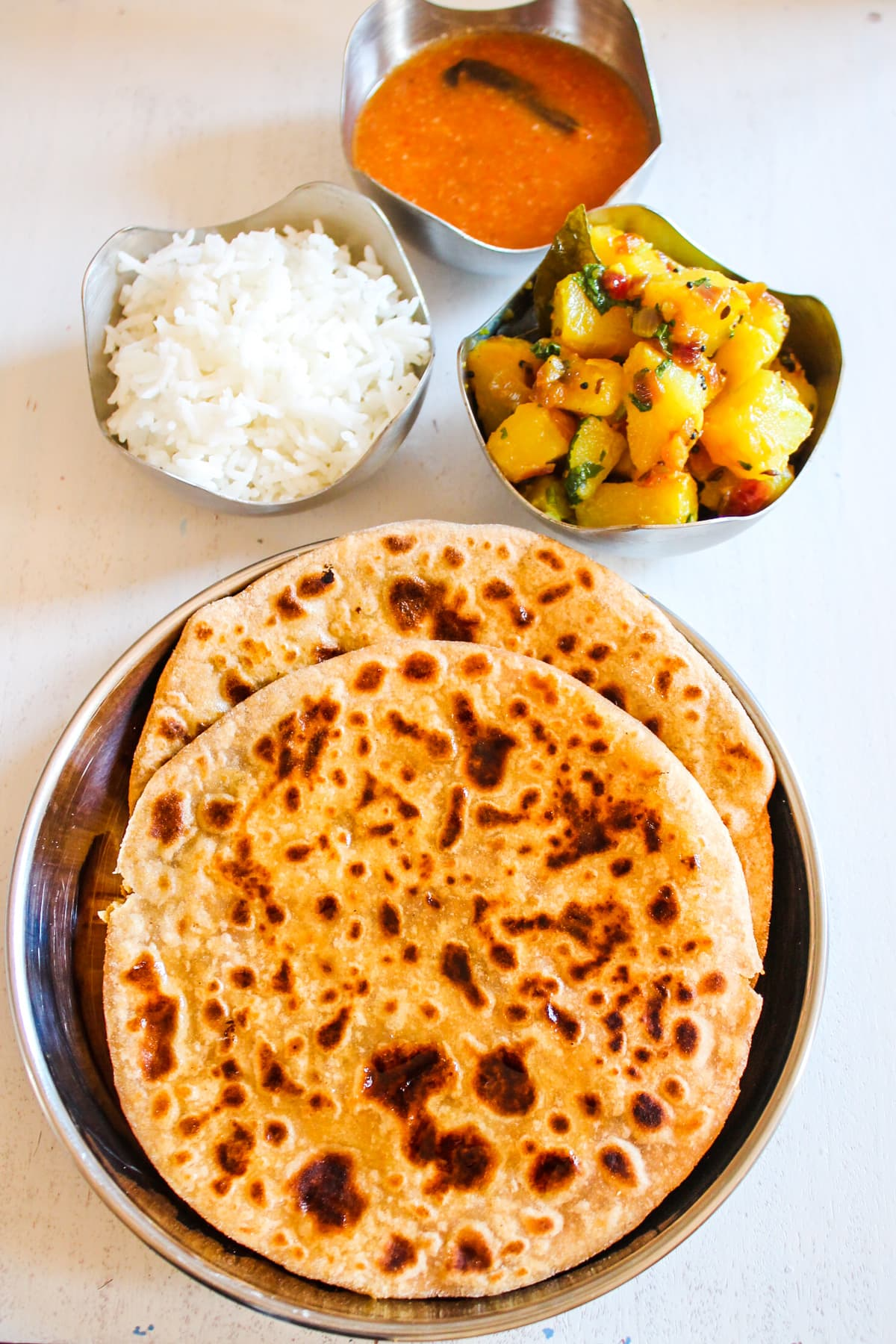 two puran poli in a steel plate with rice, bhaji and amti in steel bowl on side.
