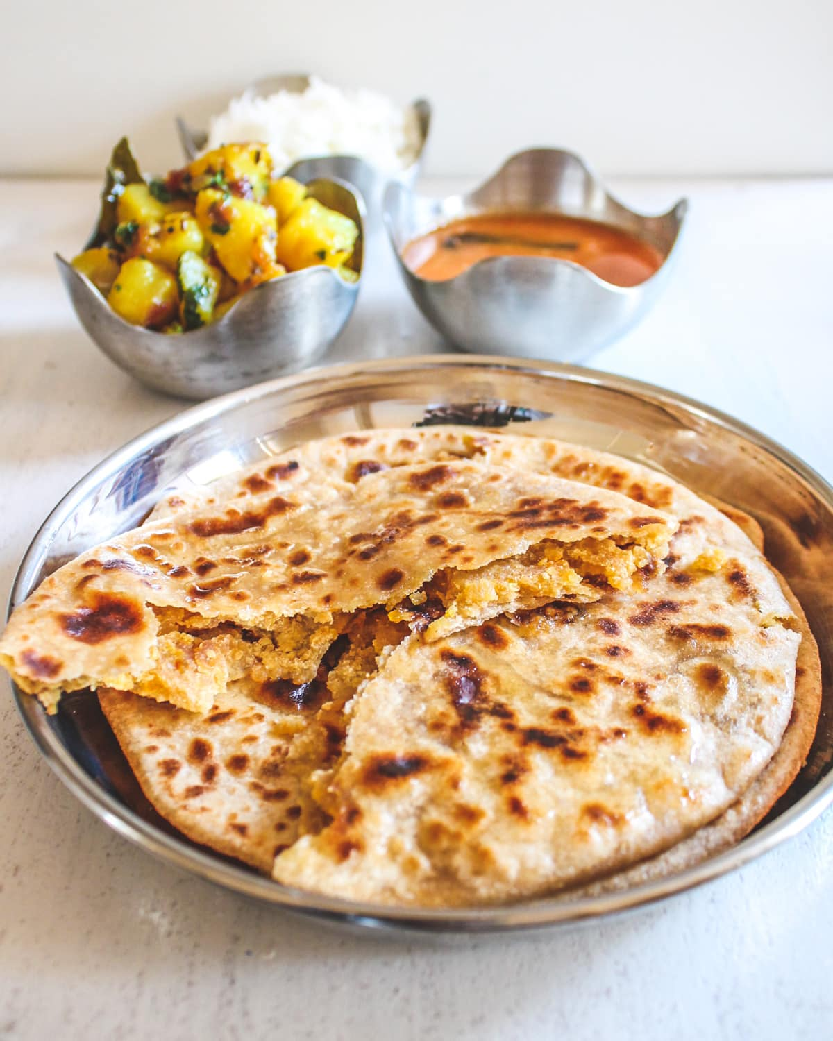 Image of puran poli cut into half to show inside stuffing. Bowls of bhaji, amti and rice on back