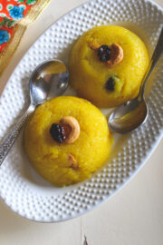 two scoops of rava kesari with garnish of cashew and raisin with 2 spoons in an oval plate