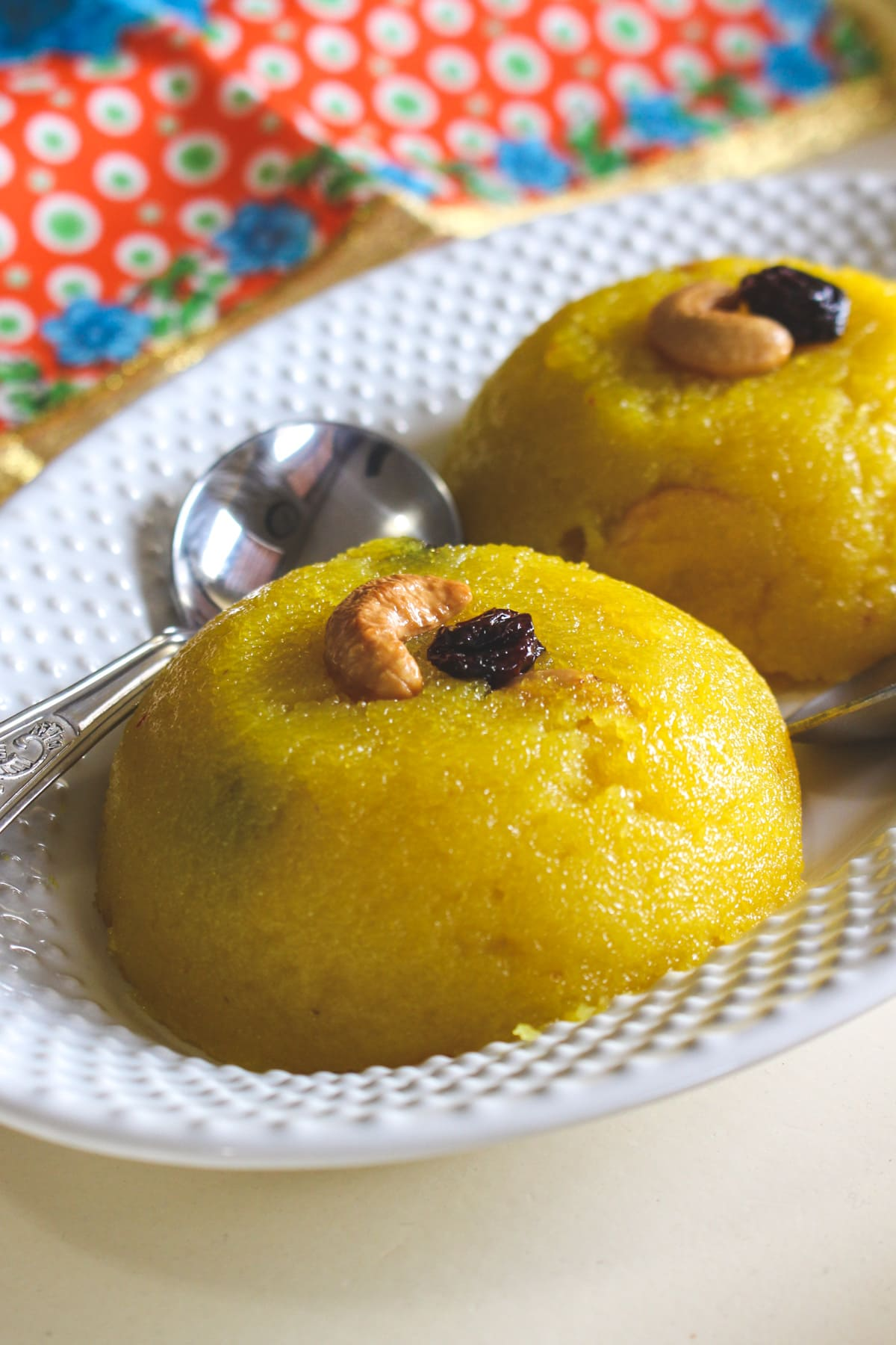 Close up of rava kesari in a plate with spoon and garnish with fried cashew and raisin