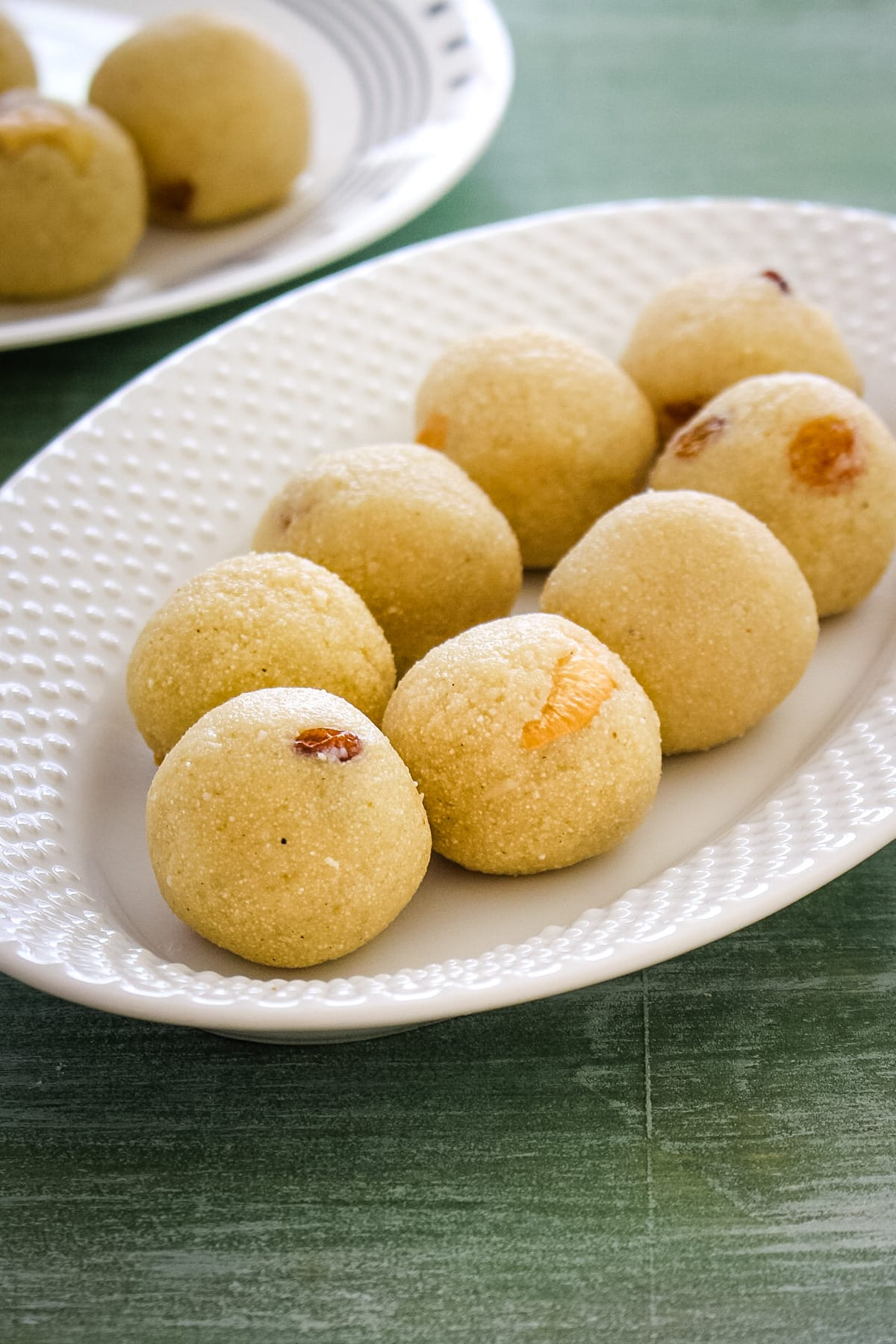 7 rava laddu in an oval plate with few more ladoos in the back in another plate