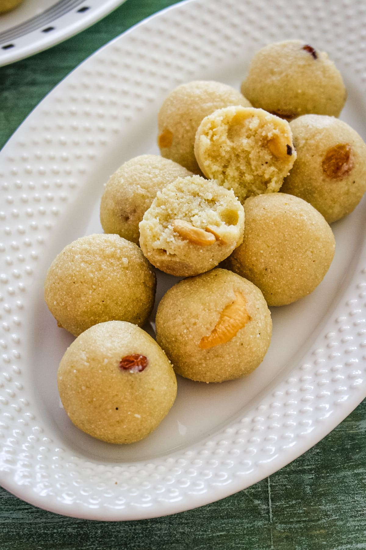 Top view of rava ladoo in oval plate with one laddu cut into half