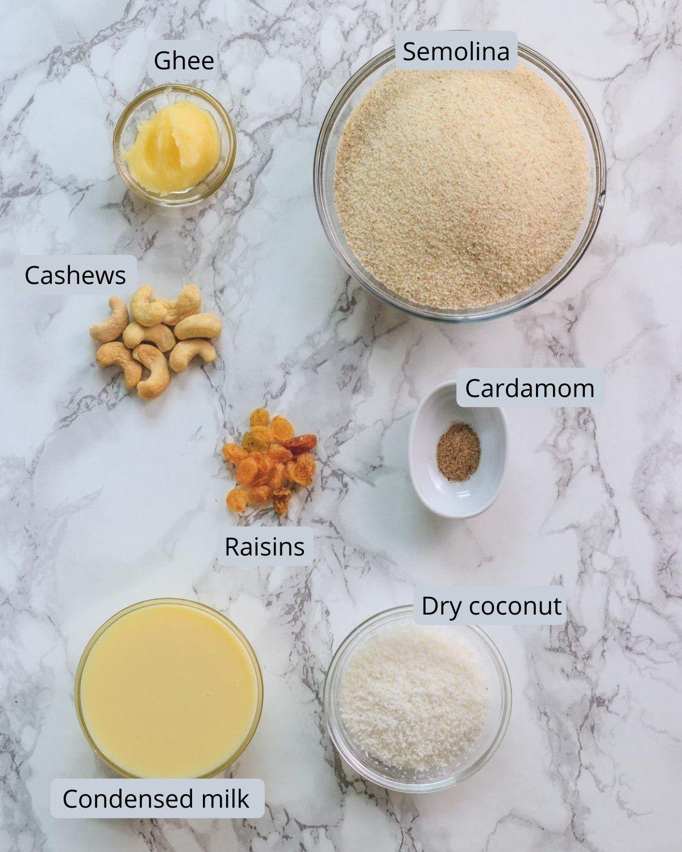 image of ingredients used in rava ladoo recipe. Includes semolina, ghee, cashews, raisins, cardamom, coconut, condensed milk