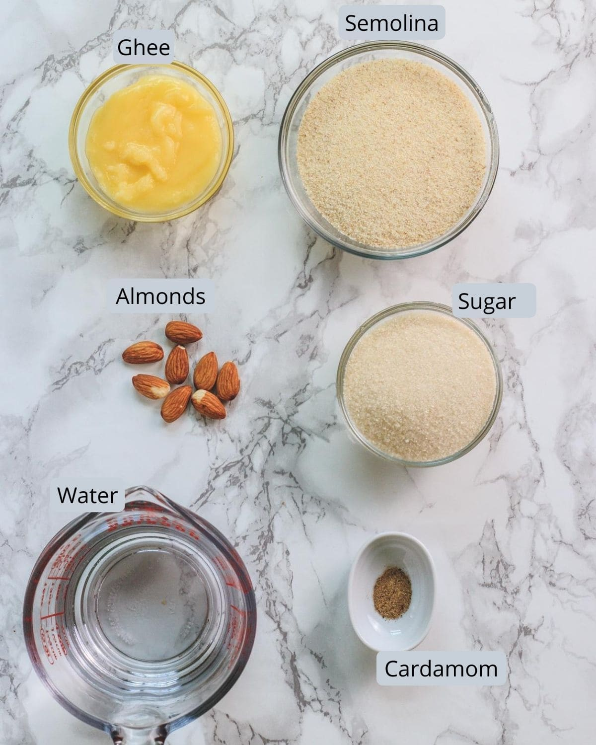 Image of ingredients used in rava sheera. Includes semolina, sugar, ghee, water, almonds, cardamom.