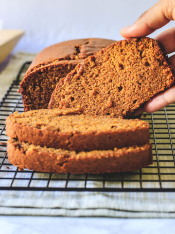 pumpkin bread on a rack lifting one slice ready to eat