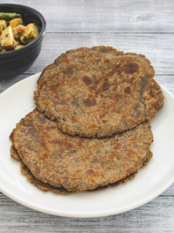 kuttu paratha in a white plate with suran sabzi on side.