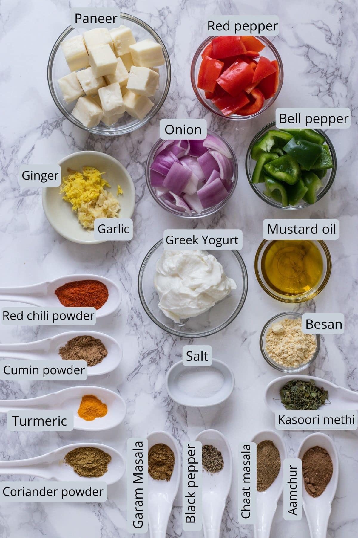 Ingredients used in paneer tikka includes greek yogurt, paneer, onion, peppers, ginger garlic paste, salt, spices, mustard oil and besan.
