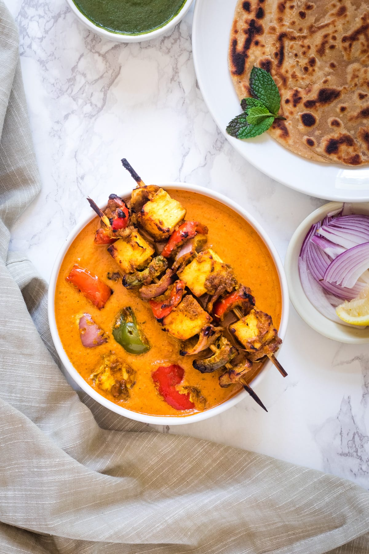 paneer tikka masala gravy with 2 skewers on the bowl, served with paratha, onions, chutney, lemon wedge