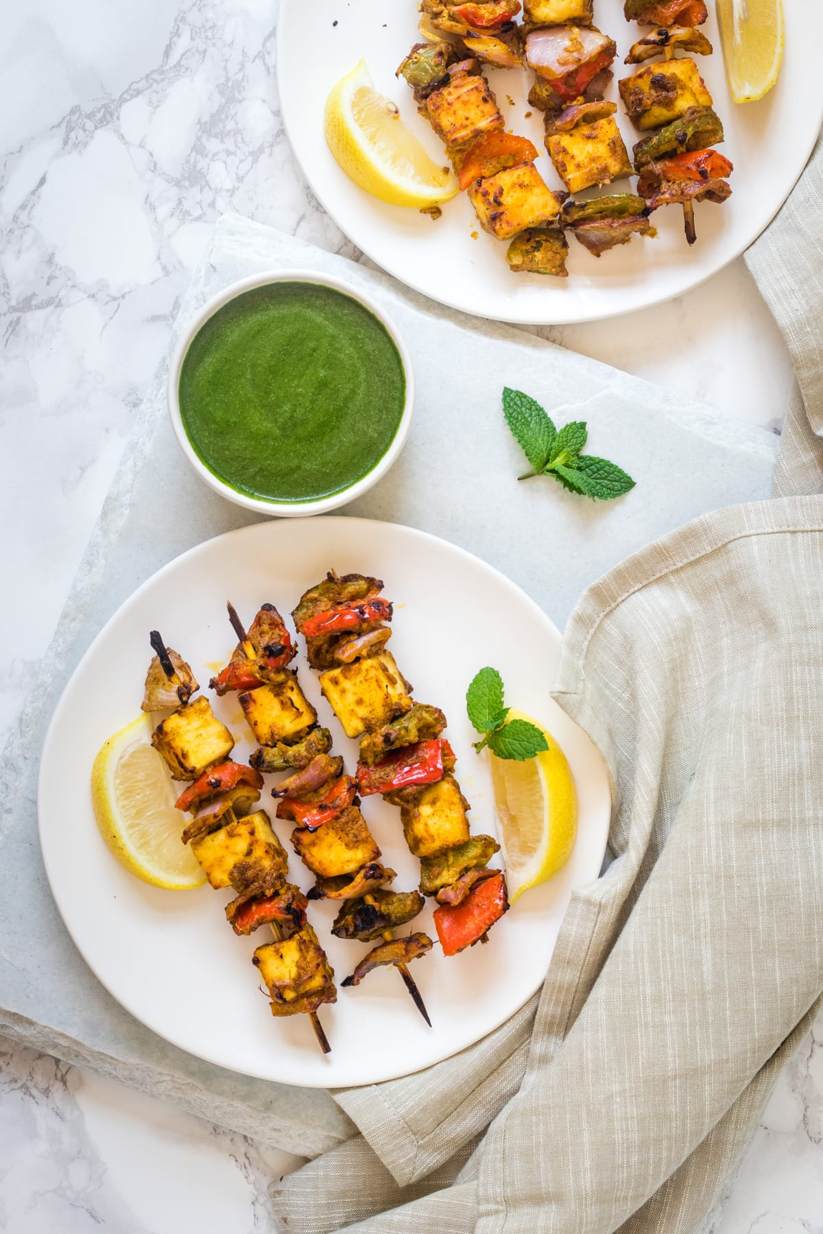 2 plates of paneer tikka served with lime wedges and green chutney with napkin on side.