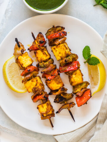 3 skewers of paneer tikka on a plate with lemon wedges and mint leaves in the plate, mint chutney in a bowl on side.