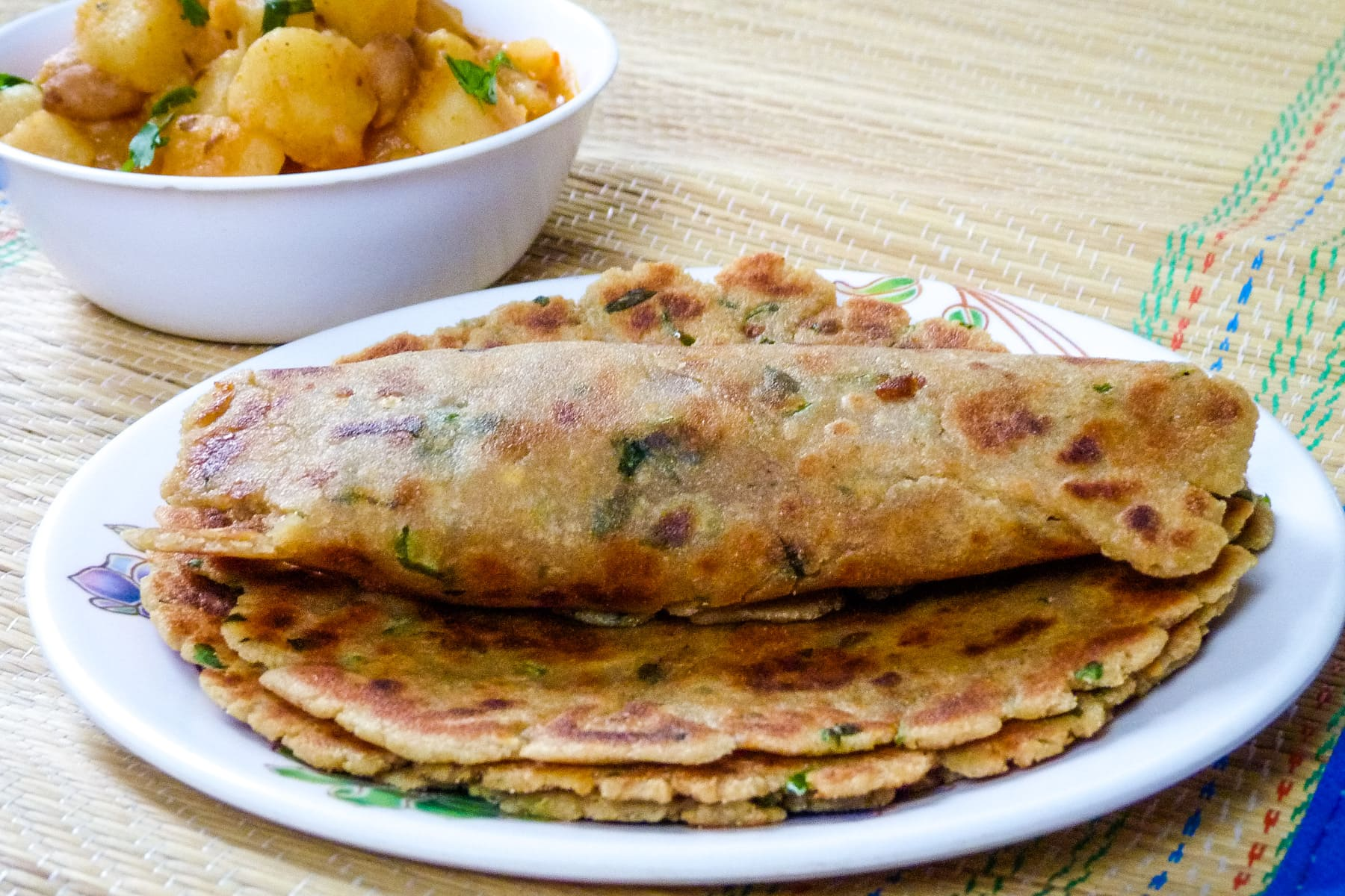 Rolled rajgira paratha on top of stack of paratha in a plate with aloo sabzi in back