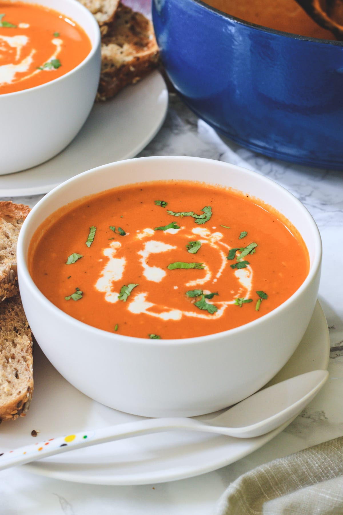 Roasted red pepper gouda soup in a bowl with side of bread.
