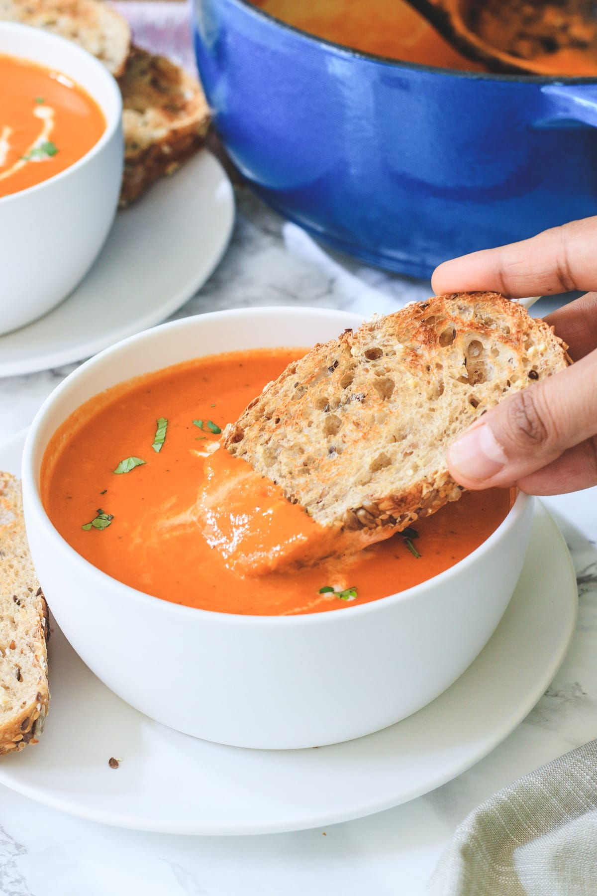 A bread dunked into the roasted red pepper soup ready to eat.