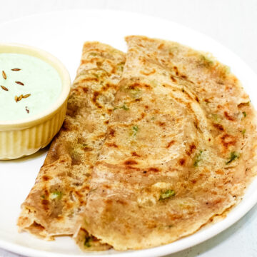 2 sabudana dosa in a white plate with coconut chutney in small bowl on the side