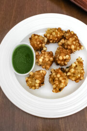 sabudana pakoda on a plate with side of green chutney