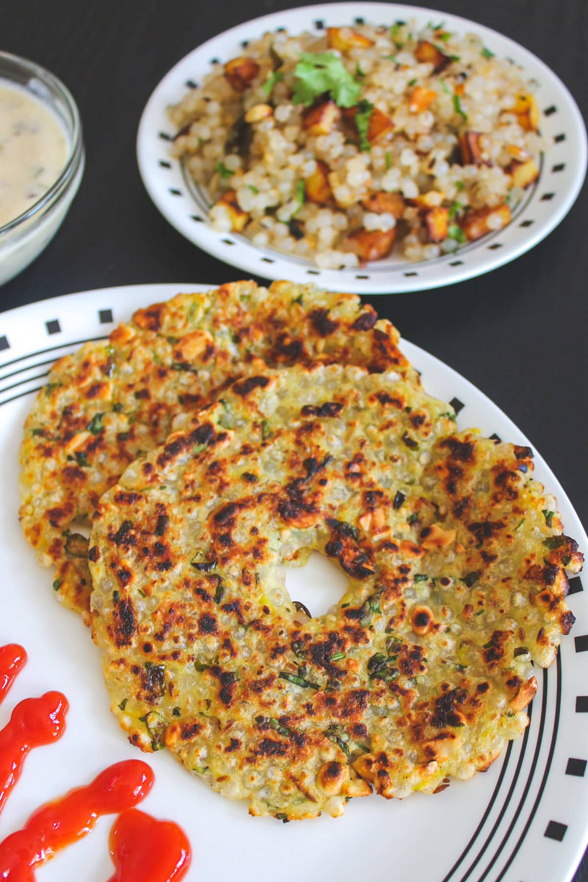 sabudana thalipeeth in a plate with ketchup on side and khichdi served in the back