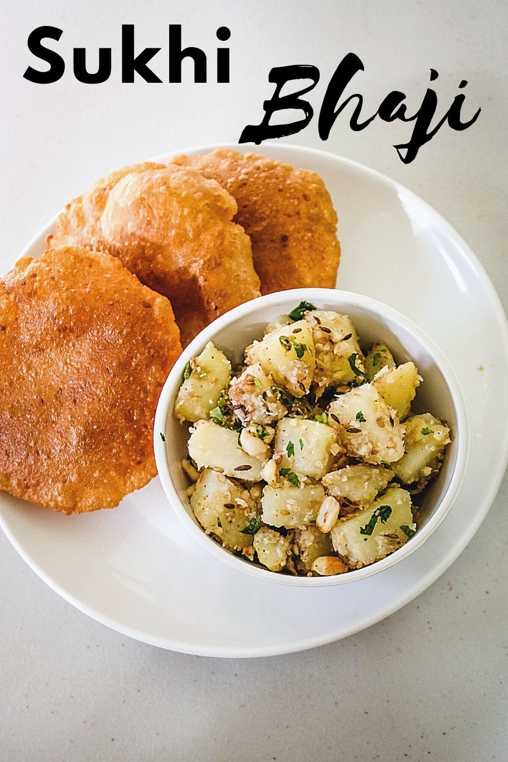 sukhi bhaji in a bowl served with puri in a plate with text on top of the image for pinterest