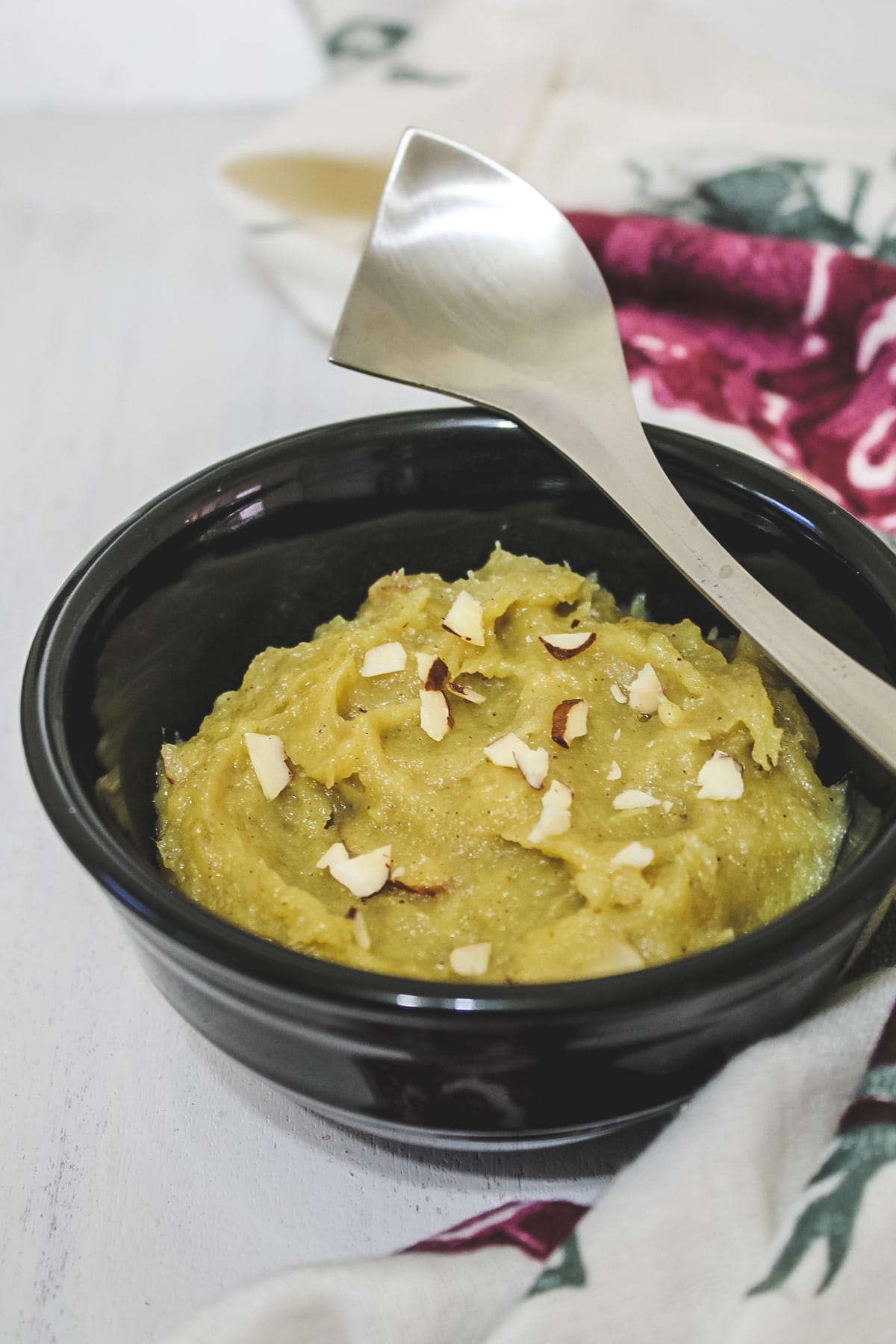 sweet potato halwa in a black bowl with a steel spoon rested on the bowl.