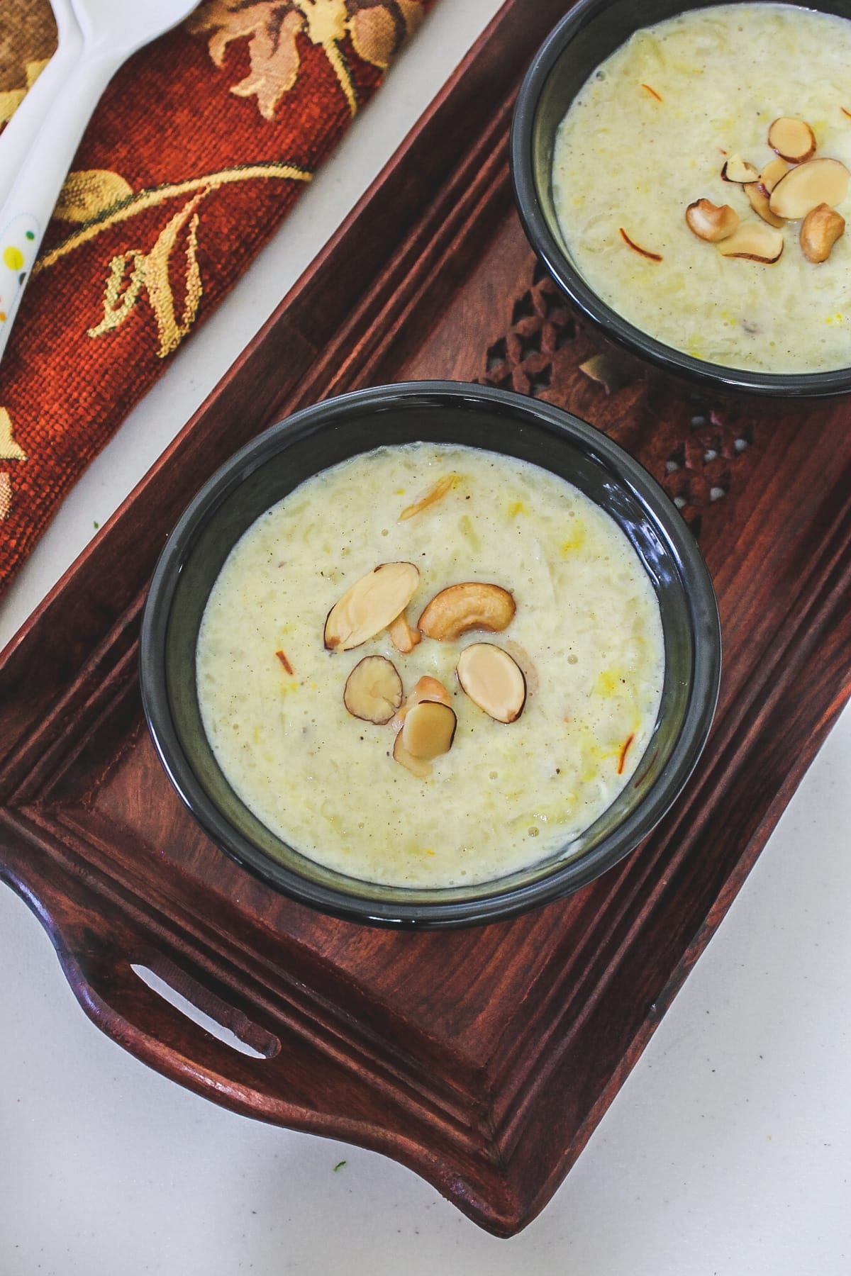 2 bowls of sweet potato kheer garnished with nuts in a wooden tray