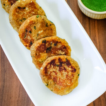 5 sweet potato tikki arranged in a plate with cilantro chutney on side