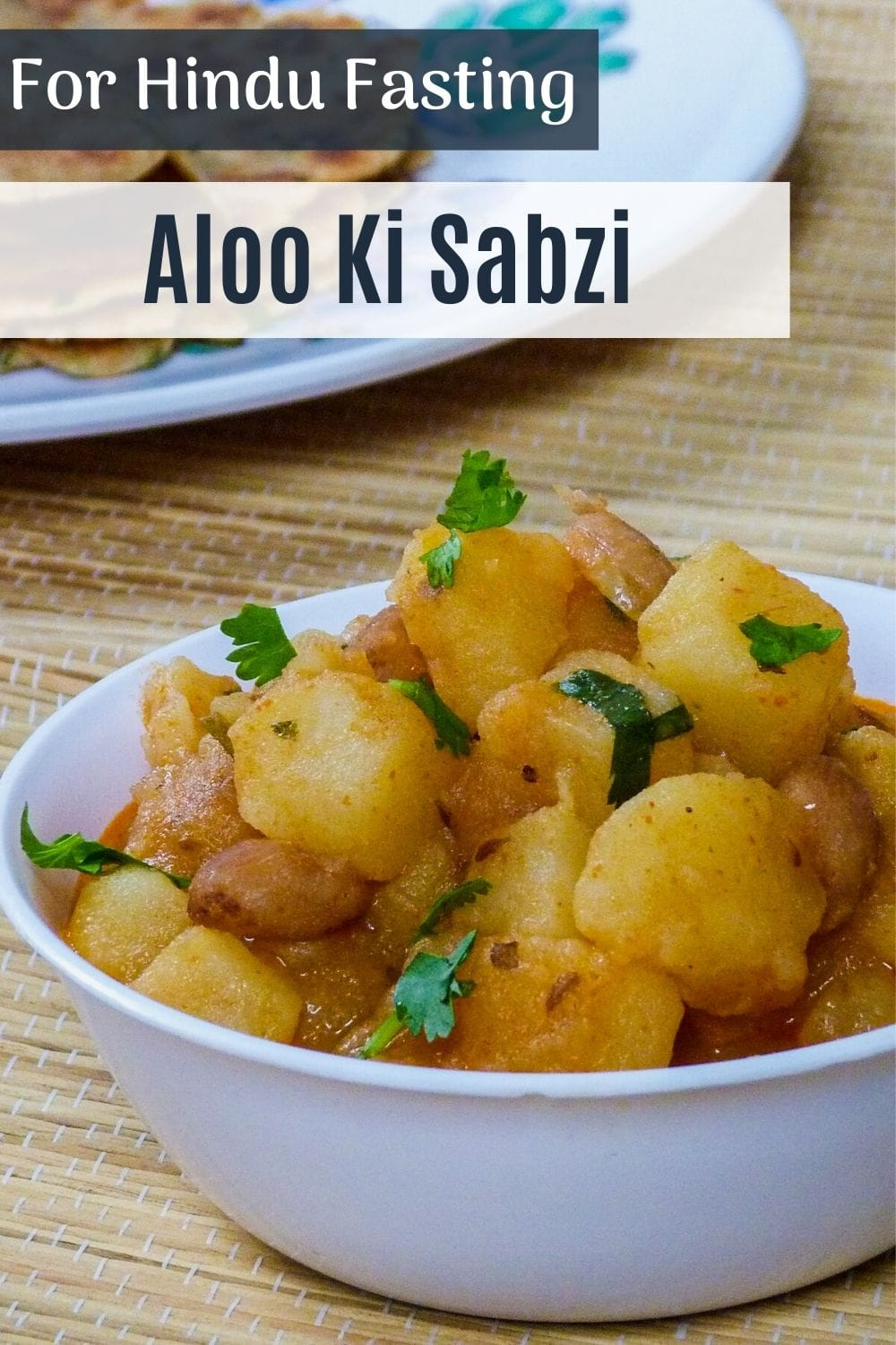 vrat wale aloo ki sabzi in a bowl with garnish of cilantro and text on top of the image for pinterest