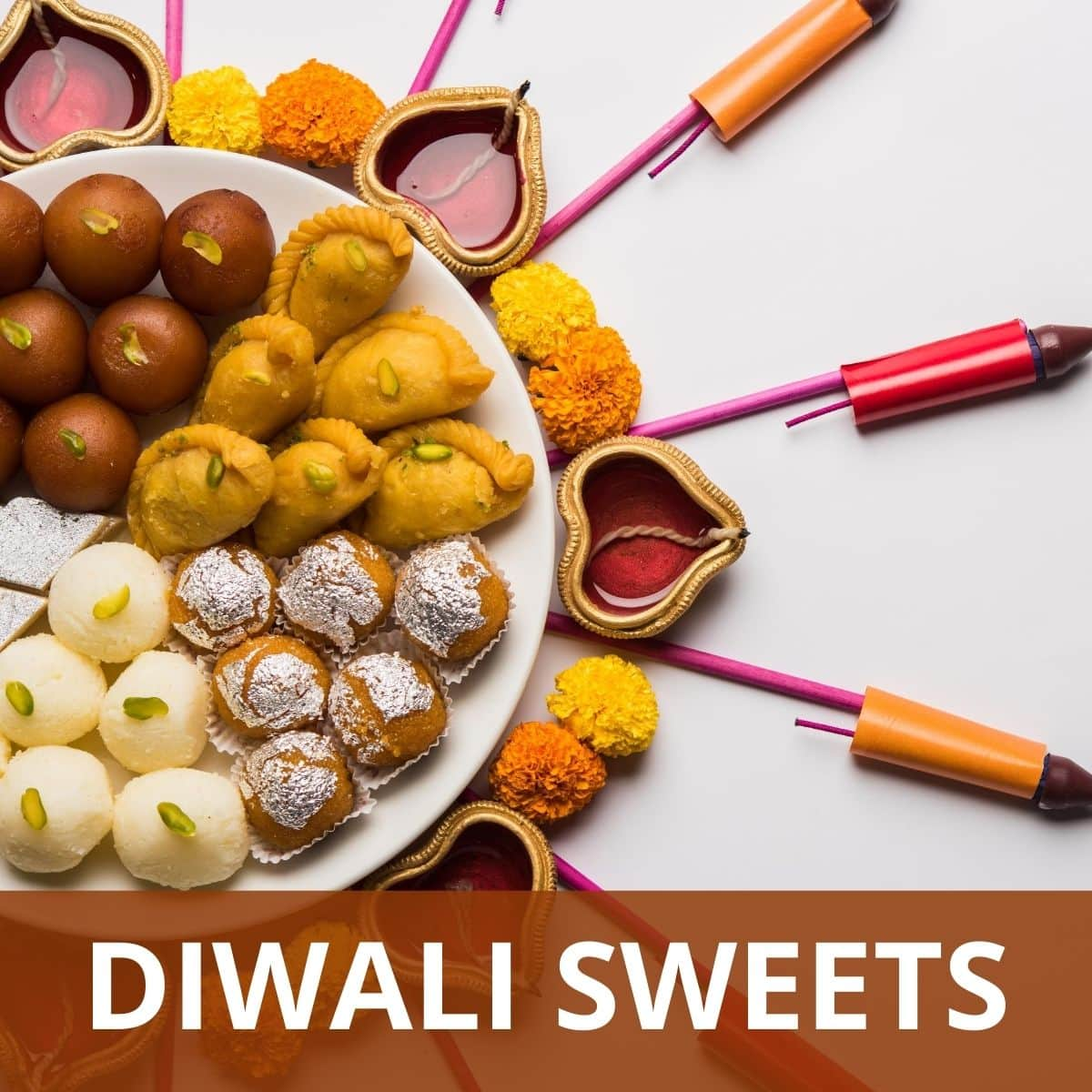 Assortment of Indian sweets in a plate with diya and firecrackers around the plate.