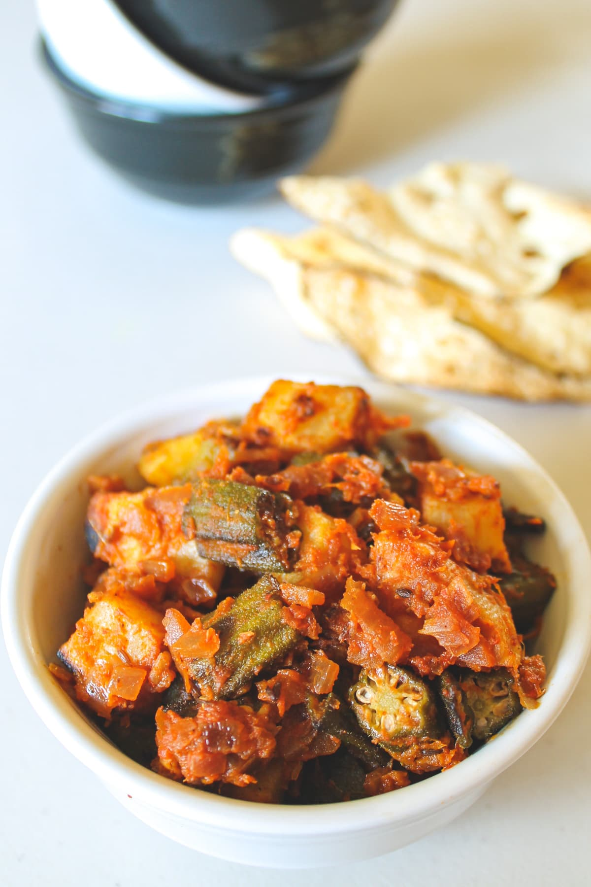 aloo bhindi served in a bowl with papad and stacked bowls in the back.