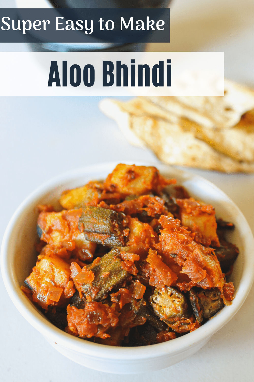Aloo bhindi served in a bowl with text on the image for pinterest.