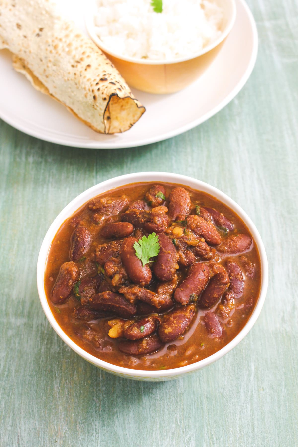 Top view of rajma in a bowl served with papad and rice.