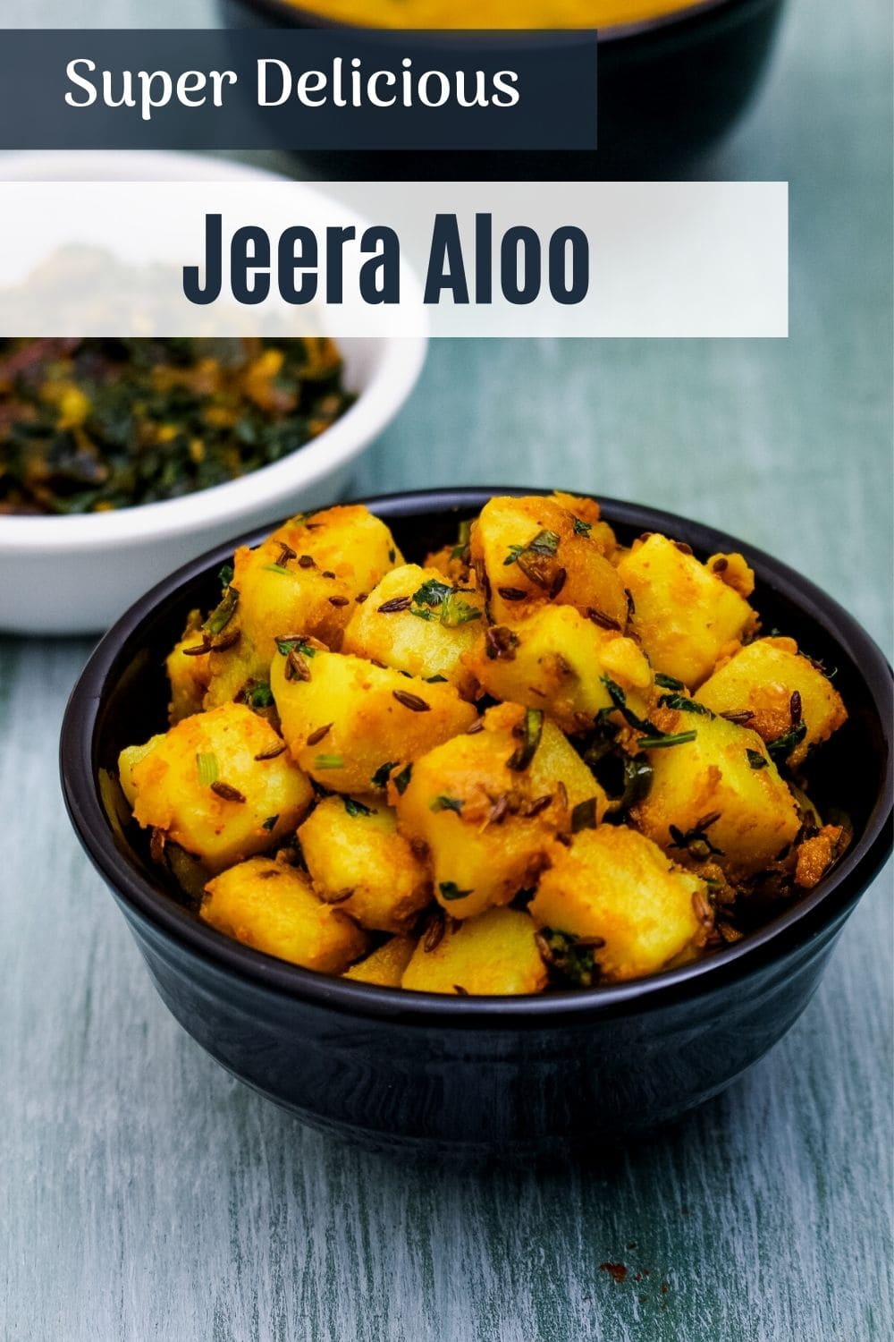 jeera aloo in a black bowl with text on the image for pinterest