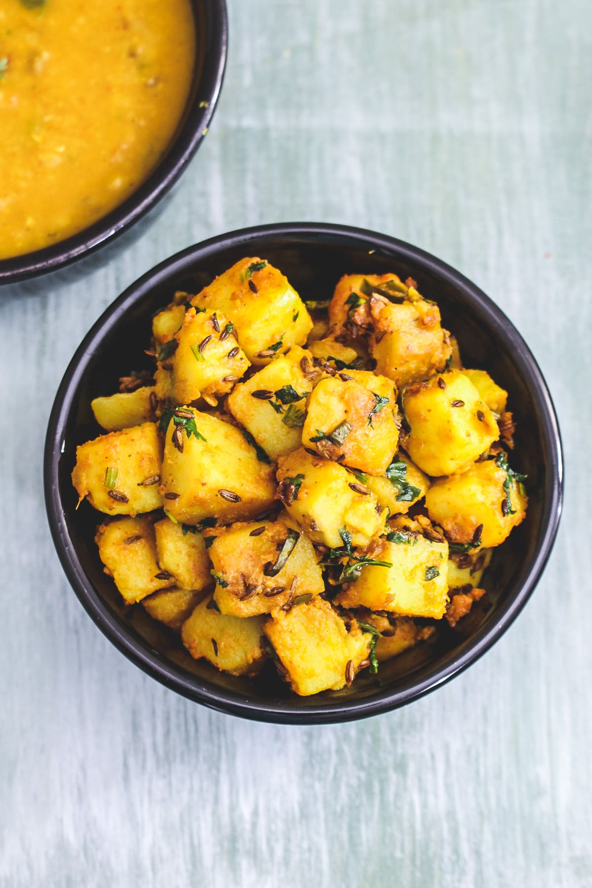 Top view of jeera aloo in a black bowl with dal served on side.