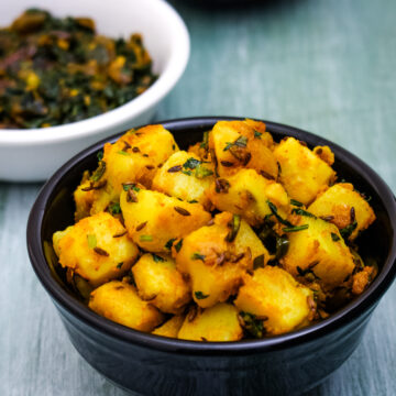 Jeera aloo served in a bowl with methi bhaji and dal in the back.
