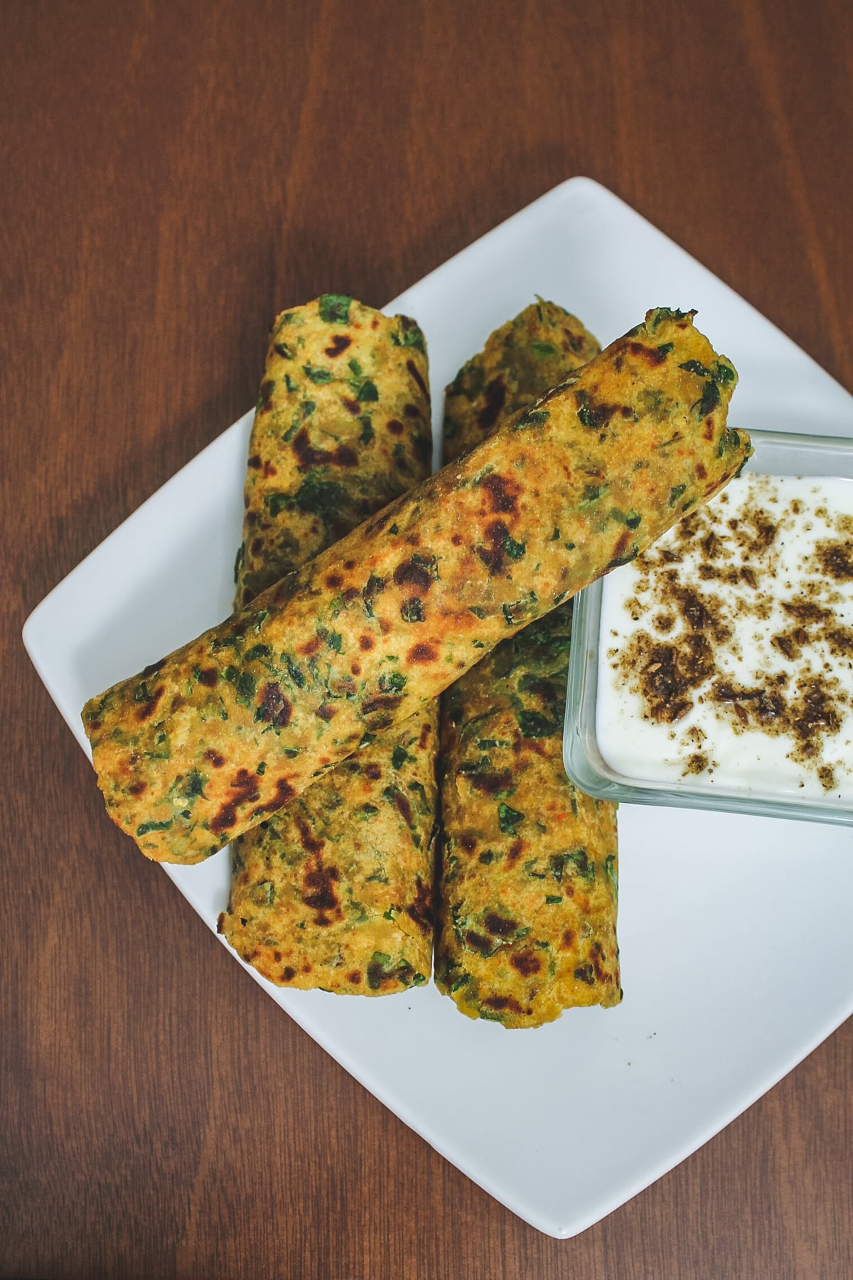 Top view of 3 methi paratha served with yogurt.