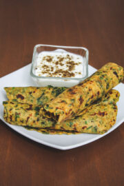 3 methi paratha roll served with a bowl of yogurt.