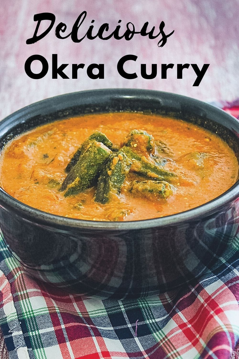 Bhindi curry in a bowl with napkin underneath with text on the image for pinterest