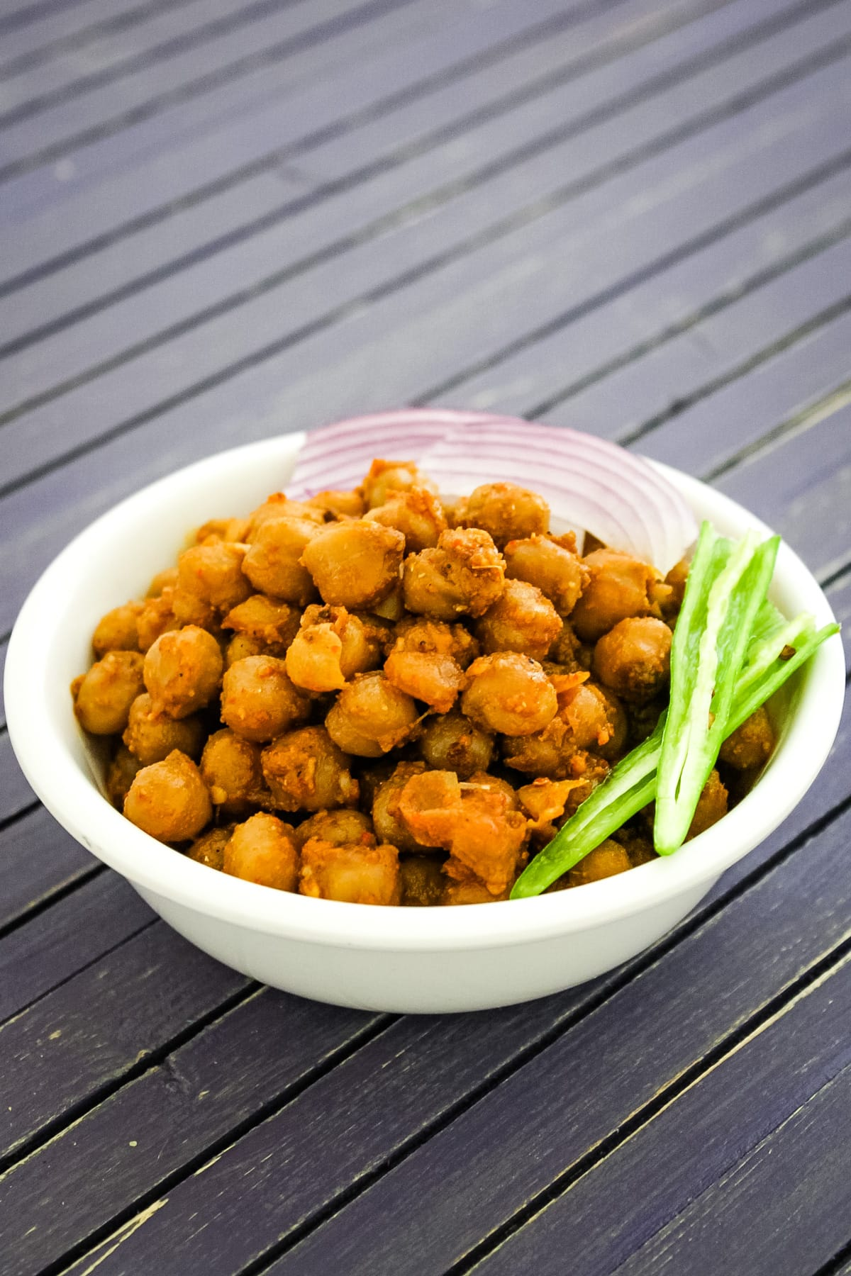 Pindi chole served in a bowl with garnish of green chili and sliced onions.
